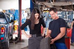 显示轮胎的技工对妇女顾客 免版税库存照片