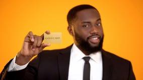 显示金卡片,俱乐部会员资格的正装的时兴的美国黑人的人 库存图片