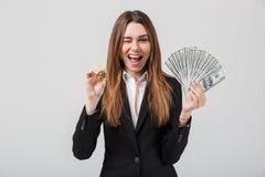 显示金黄bitcoin和美元的快乐的少妇在手 免版税库存照片