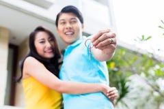 显示钥匙的中国夫妇对他们新的家 免版税库存图片