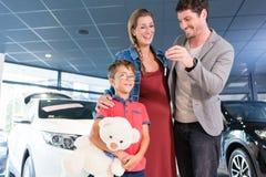显示钥匙的家庭对最近被买的汽车在陈列室 免版税库存照片