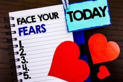 显示面孔您的恐惧的公告文本 在笔记本嘘写的概念意思挑战恐惧Fourage信心勇敢的勇敢 免版税库存图片