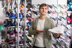 显示鞋子的年轻人在体育商店 免版税库存照片