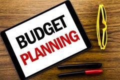显示预算计划的文字文本 在片剂膝上型计算机写的财政预算的企业概念,与VA的木背景 库存照片