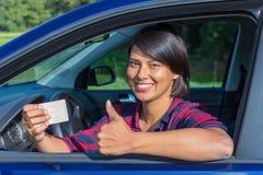 显示驾照的少妇在汽车 免版税库存图片