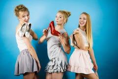 显示高跟鞋鞋子的三名妇女 免版税库存照片