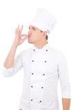 显示鲜美好标志的愉快的年轻人厨师被隔绝在白色 免版税库存图片