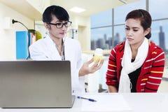 显示黄色解决方法的医生对患者 库存照片