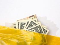 显示从一个黄色塑料袋的美元 免版税库存照片