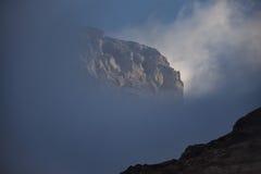 显示从多云面纱的鬼的山峰 免版税库存图片