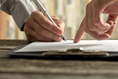 显示他新的雇员在哪里的雇主特写镜头签署em 免版税库存图片