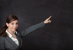 显示黑板的衣服的妇女 免版税库存照片