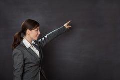 显示黑板的衣服的妇女 库存照片