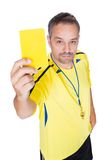 显示黄牌的足球裁判 免版税库存图片