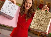 显示购物袋的愉快的少妇在圣诞节厨房 库存图片