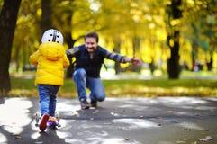 显示他的小孩儿子如何的中年父亲乘坐一辆滑行车在秋天公园 库存照片