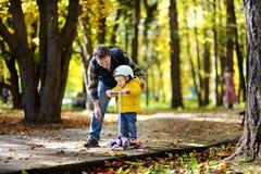 显示他的小孩儿子如何的中年父亲乘坐一辆滑行车在秋天公园 免版税库存图片