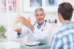 显示他的患者脊椎模型的医生 库存照片