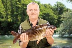 显示他的抓住的成熟渔夫支持河 免版税图库摄影
