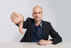 显示他的拇指的恼怒的秃头商人下来 库存照片
