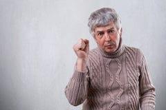 显示他的拳头的一个英俊的成熟人,当是恼怒和激怒时 有显示他的不满情绪机智的皱痕的一名老人 免版税图库摄影