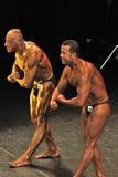 显示他们的最肌肉的姿势的两个男性爱好健美者 免版税库存照片