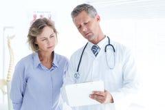 显示他的笔记的医生对他的患者 免版税库存照片