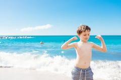 显示他的肌肉的确信的小男孩,当使用在海滩时 图库摄影