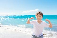 显示他的肌肉的确信的小男孩,当使用在海滩时 免版税库存图片