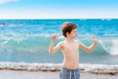显示他的肌肉的确信的小男孩,当使用在海滩时 免版税库存照片