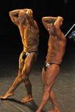 显示他们的胃肠和大腿的男性爱好健美者 免版税库存图片
