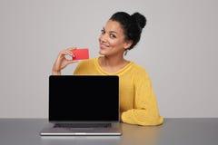 显示黑膝上型计算机屏幕和信用卡的妇女 免版税图库摄影