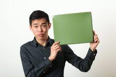 显示绿色拷贝空间箱子的年轻亚裔人 免版税图库摄影