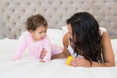 显示黄色鸭子的愉快的浅黑肤色的男人对她的婴孩 图库摄影