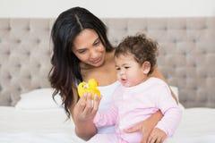 显示黄色鸭子的愉快的浅黑肤色的男人对她的婴孩 库存图片