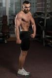 显示他训练有素的身体的健身房的人 库存图片