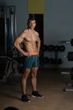 显示他训练有素的身体的健身房的人 图库摄影