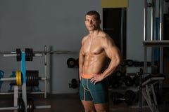 显示他训练有素的身体的健身房的人 免版税图库摄影