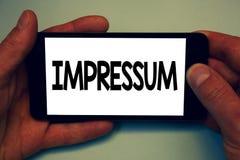 显示Impressum的概念性手文字 陈列被打动的被刻记的版本记录德国声明归属作者的企业照片 免版税库存照片