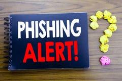 显示Phishing戒备的手写的文本 企业在笔记薄便条纸写的欺骗警告危险的概念文字,木b 免版税库存图片