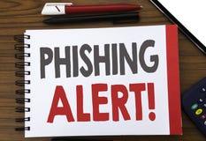 显示Phishing戒备的手写的文本 企业在笔记薄便条纸写的欺骗警告危险的概念文字,木b 免版税库存照片
