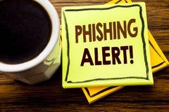显示Phishing戒备的手写的文本 在木木头的稠粘的便条纸写的欺骗警告危险的企业概念 库存图片