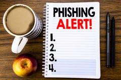 显示Phishing戒备的手写的文本 在笔记薄在木struc的便条纸写的欺骗警告危险的企业概念 免版税库存图片