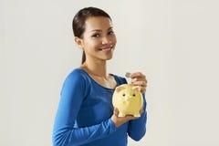 显示piggybank和欧洲硬币的亚裔女孩 库存照片