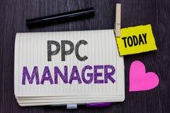 显示Ppc经理的文本标志 登广告者每次支付费他们的广告一的概念性照片是点击的开放笔记本凝块 图库摄影
