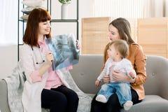 显示X-射线图象的年轻女性医生对有快乐的女儿的年轻母亲在诊所 库存照片
