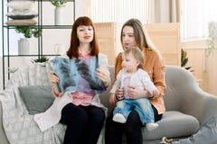 显示X-射线图象的年轻女性医生对有快乐的女儿的年轻母亲在诊所 免版税库存照片