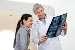 显示X-射线报告的放射学家对患者 免版税库存图片