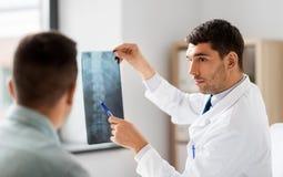 显示X-射线的医生对患者在医院 库存图片