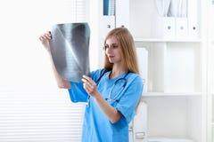 显示X-射线的女性医生在医院 免版税库存照片
